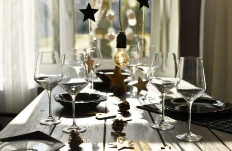 długi stół z czarną zastawą i szklanymi kieliszkami przy ozdobach świątecznych