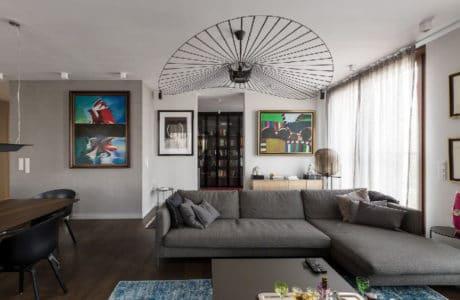mieszkanie z ciemno brązową deską na podłodze wraz z szarymi meblami i kolorowymi obrazami na ścianach