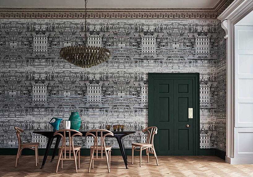 fototapety 3d czarno-biała panorama kamienic wjadalni zczarnym stołem drewnianymi krzesłami izielonymi drzwiami