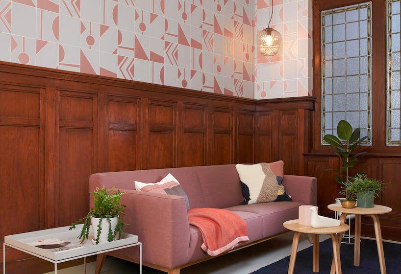 fototapety 3d wnieregularny figury geometryczne nad drewnianym wykończeniem iróżową sofą
