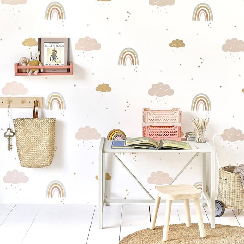 wyjątkowa tapeta do pokoju dziecięcego ztęcza imałymi chmurami jako tło dla małego stolika ztaboretem