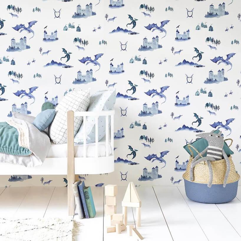 wyjątkowa tapeta do pokoju dziecięcego zez smokami izamkami jako tło dla białego łóżeczka dla dzieci