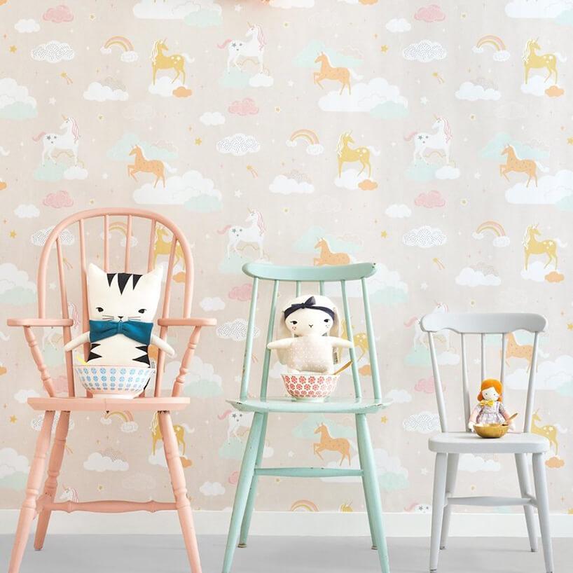 wyjątkowa tapeta do pokoju dziecięcego zjednorożcami chmurkami itęczami na tle trzech krzeseł zprzytulankami