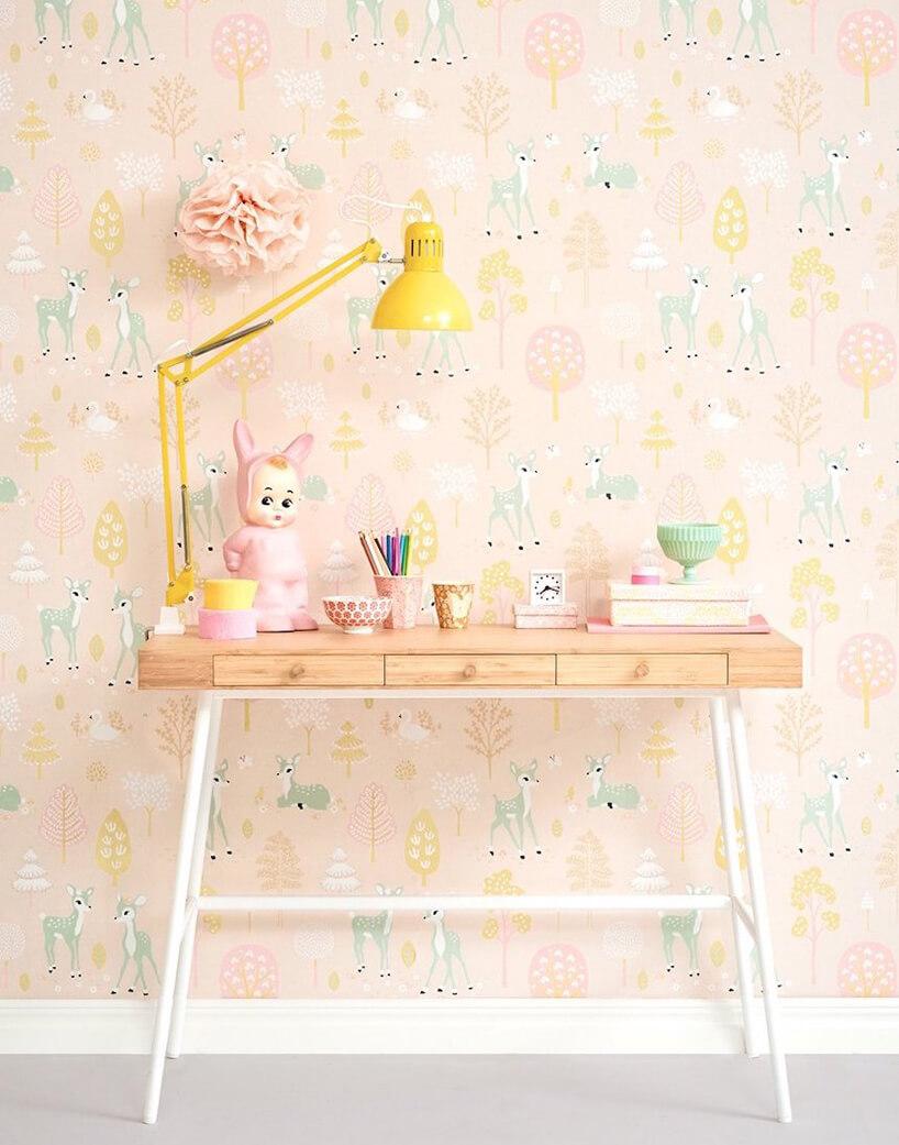 wyjątkowa tapeta do pokoju dziecięcego zmałymi jelonkami idrzewami jako tło dla drewnianego biurka zżółta lampką