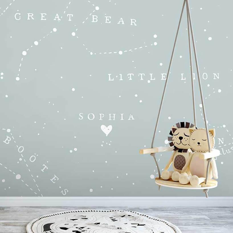 wyjątkowa tapeta do pokoju dziecięcego szara tapeta zgwiazdozbiorami iich nazwami jako tło dla huśtawki zdwoma przytulankami