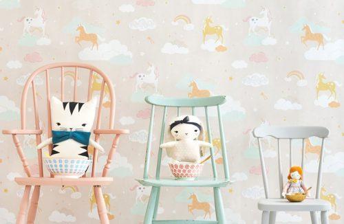 wyjątkowa tapeta do pokoju dziecięcego z jednorożcami chmurkami i tęczami na tle trzech krzeseł z przytulankami