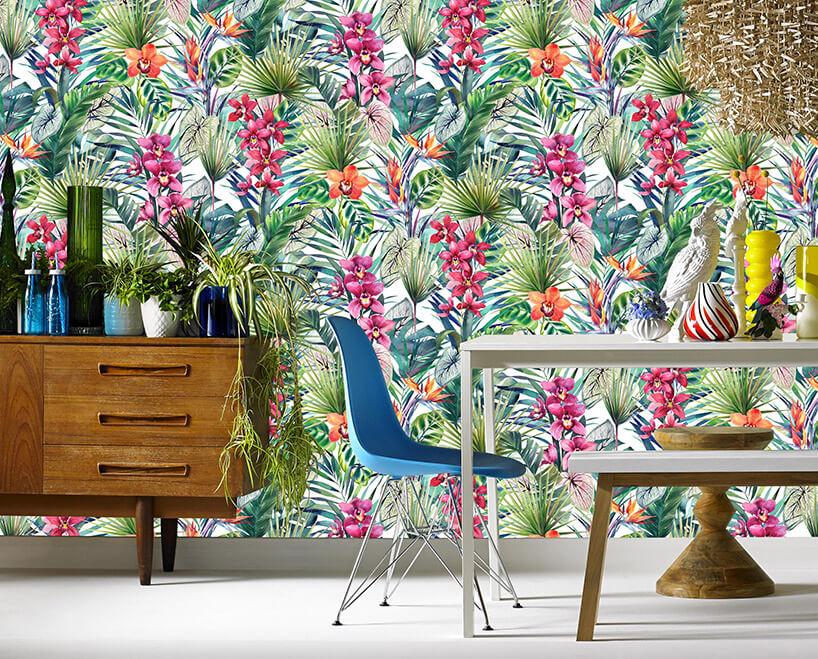 stół zławeczką ikrzesłem na tle wielokolorowa tapeta zmotywem roślinności tropikalnej