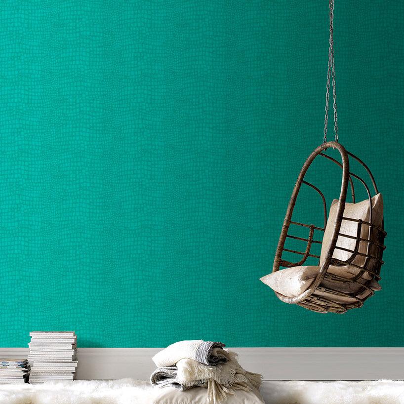 podwieszany siedzisko wkształcie kosza na tle turkusowej tapety