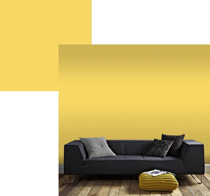 czarna sofa na tle żółtej tapety