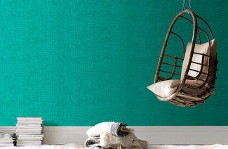 podwieszany siedzisko w kształcie kosza na tle turkusowej tapety