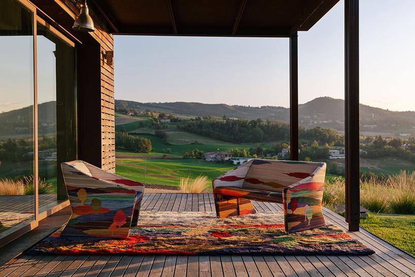 zestaw kolorowych mebli na dywanie zkolekcja Shaded Stripes od Missoni Home na drewnianym tarasie