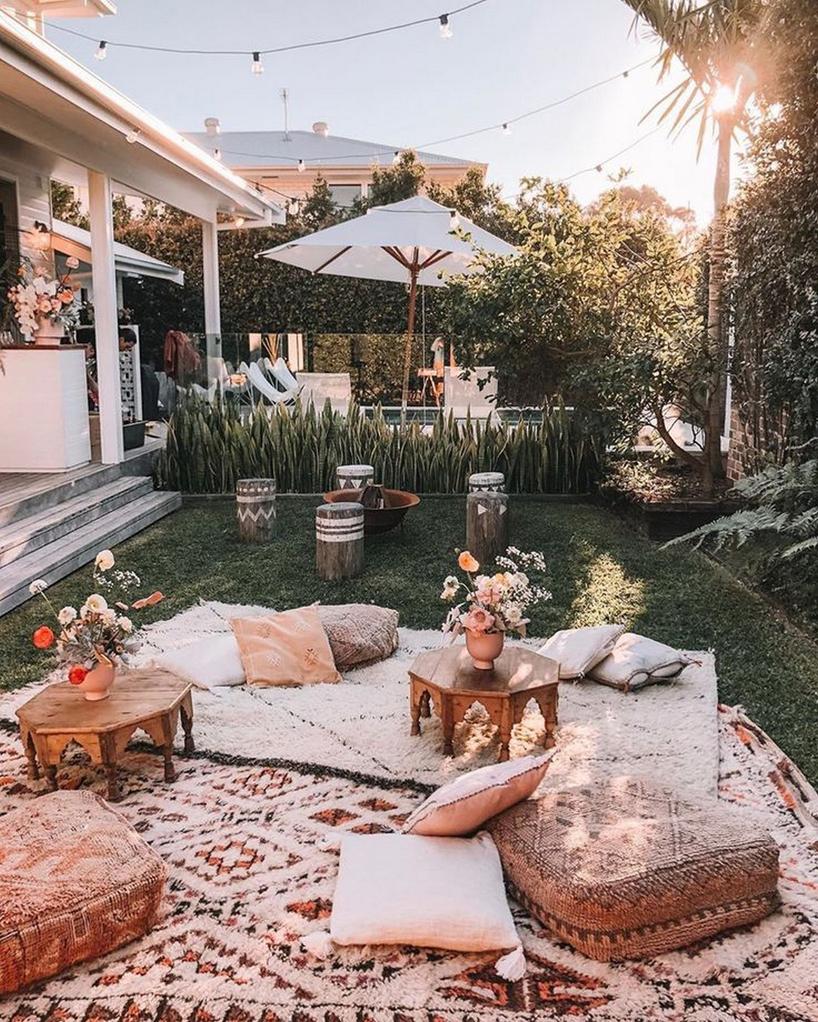 mały ogródek zrozłożonym dywanem zpoduszkami imałymi drewnianymi stolikami