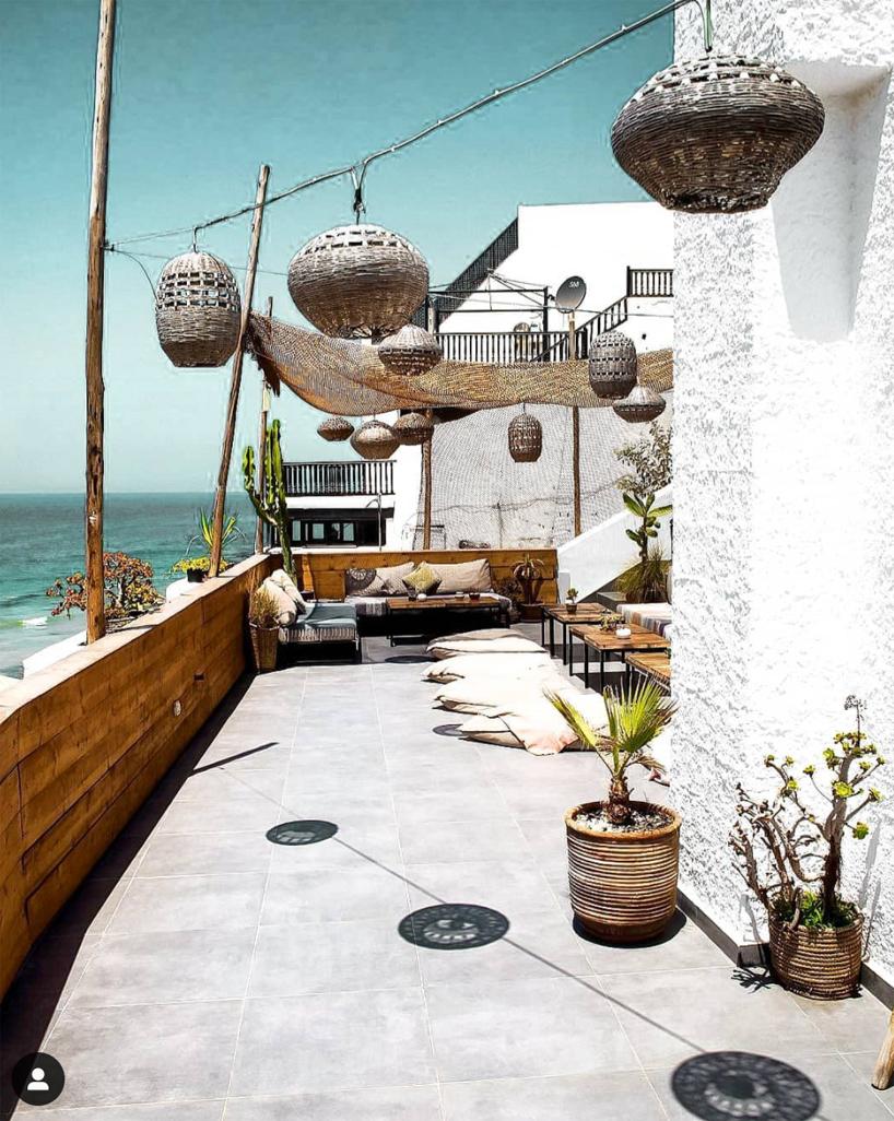 duży kamienny taras zdrewnianą balustradą na tle morza