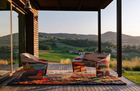 zestaw kolorowych mebli na dywanie z kolekcja Shaded Stripes od Missoni Home na drewnianym tarasie