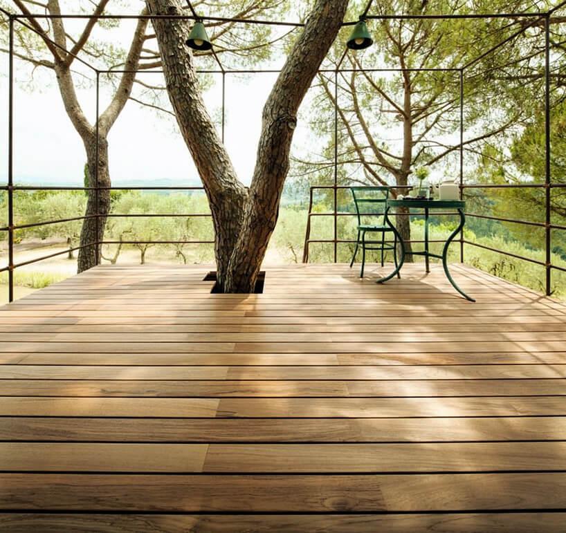drewniany taras zmetalowym stolikiem ikrzesłem wkoronach drzew