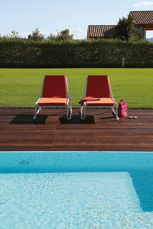 drewniany taras nad basenem zdwoma leżakami