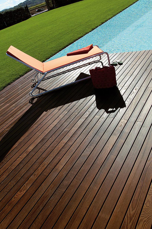drewniany taras wbrązowym kolorze nad basenem zpomarańczowym leżakiem