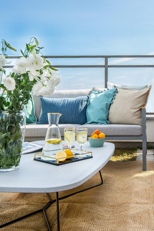 drewniany taras zniskim białym stolikiem na tle szarej sofy zpoduszkami