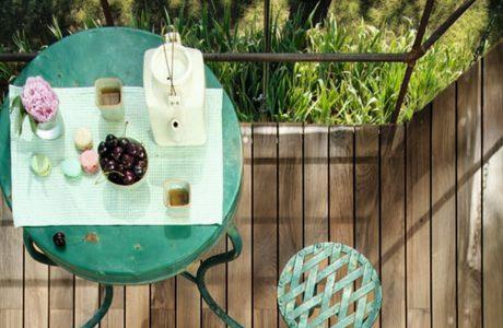 drewniany taras oraz stary stolik i stołek w zielonym kolorze