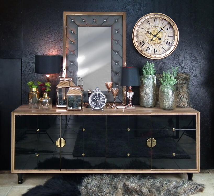 elegancka komoda zczarnym błyszczącym frontem ze złotymi dodatkami pod lustrem zgrubą plisowaną skórzana ramą