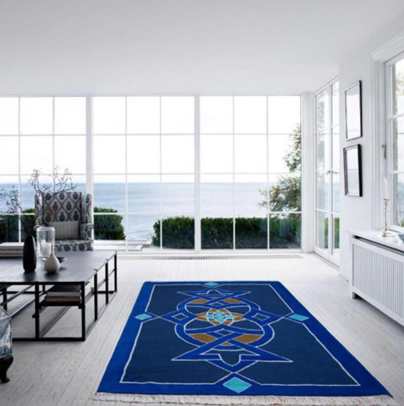 niebieski dywan na białej podłodze wsalonie na tle przeszklonej ściany zwidokiem na morze