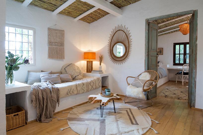 biały salon wstary domu zkamiennym siedziskami pod sufitem wykończonym strzechą