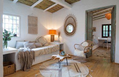 biały salon w stary domu z kamiennym siedziskami pod sufitem wykończonym strzechą