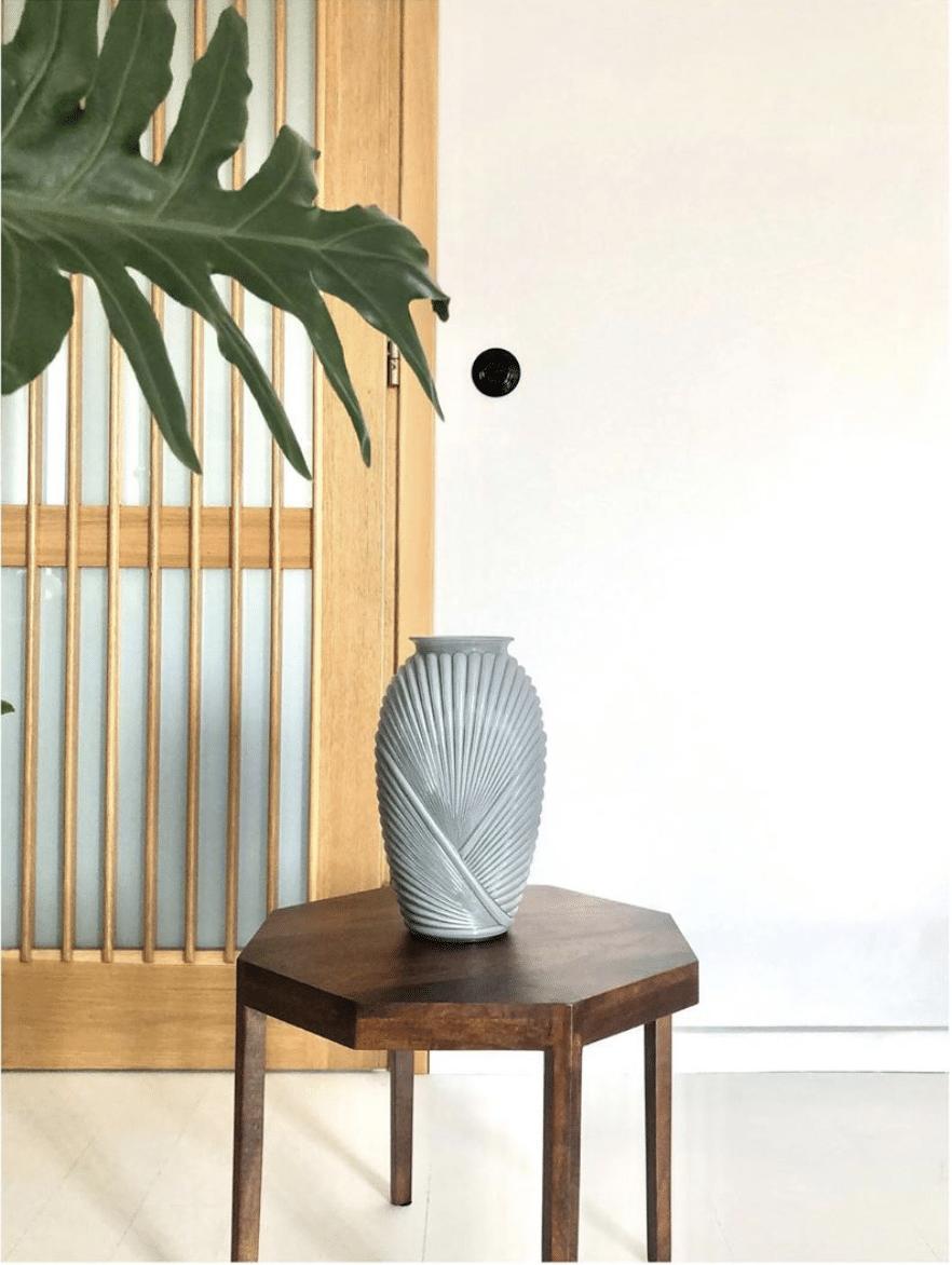 szara waza na drewnianym stole pod liściem kwiatu
