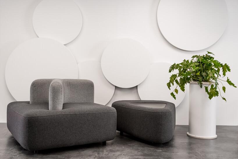dwa szare nowoczesne siedziska obok wysokie donicy zkwiatem na tle białych okrągłyach dekaoracji na ścianie