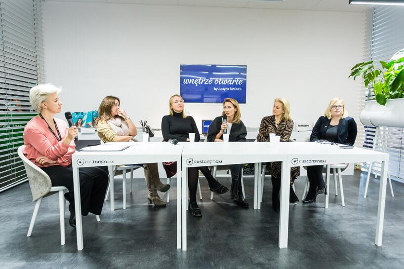 sześc kobiet siedzących przy 3 stołach