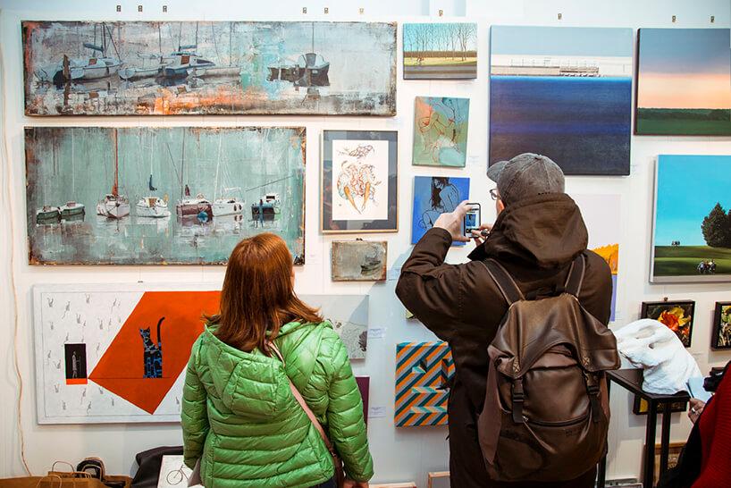 odwiedzający Targi Sztuki Dostępnej oglądający rożne obrazy na jednym ze stoisk