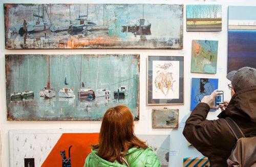 dwie osoby oglądające ekspozycję na Targach Sztuki Dostępnej 2019