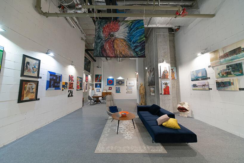 białe wnętrze galerii Targów Sztuki Dostępnej szarą podłogą idługą granatową sofą