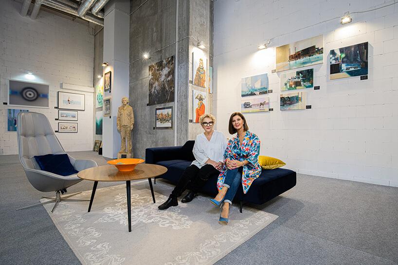 dwie kobiety Lena Szwed-Strużyńska iEwa Mierzejewska siedzące na granatowej sofie wgalerii Targów Sztuki Dostępnej