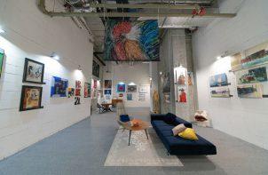 białe wnętrze galerii Targów Sztuki Dostępnej szarą podłogą i długą granatową sofą