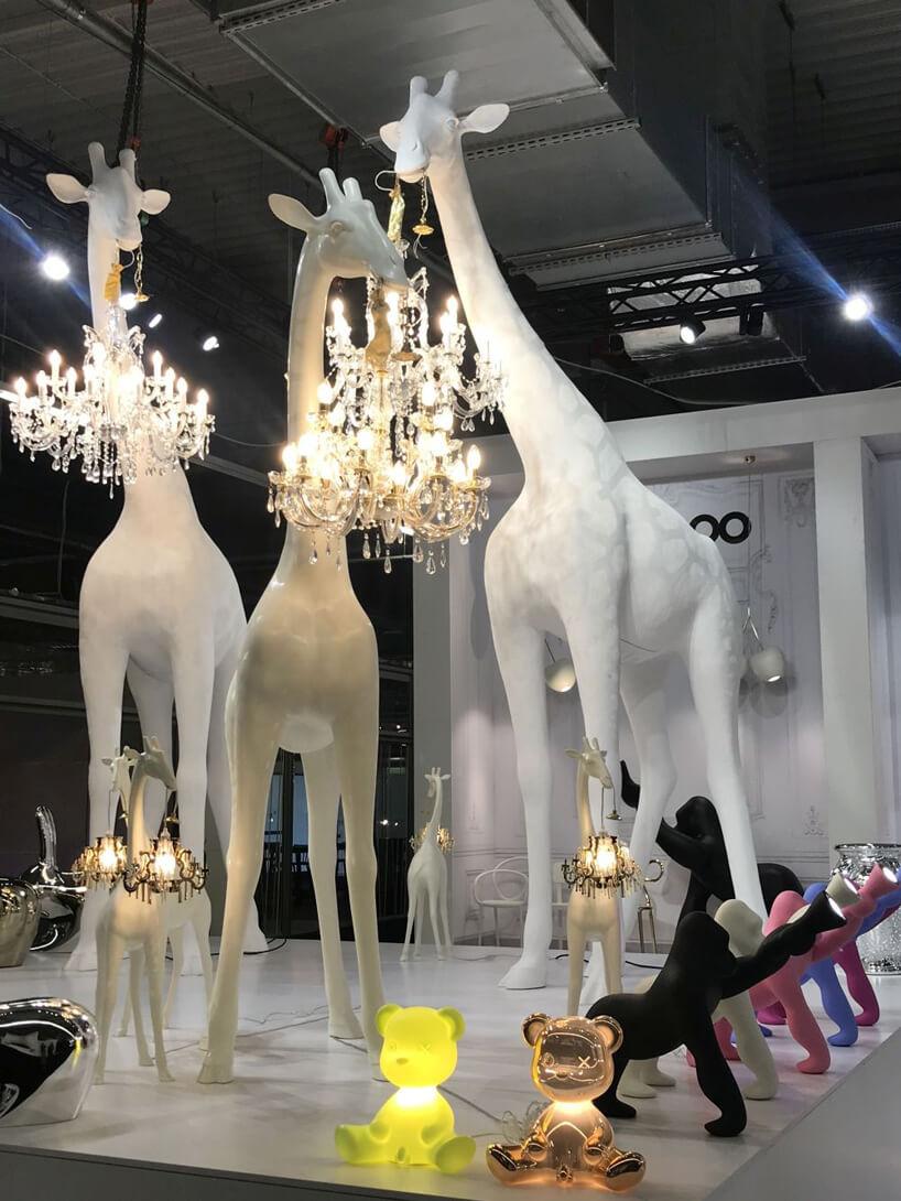 trzy białe duże żyrafy trzymające żyrandole na stosiku Stoisko QeeBoo podczas Warsaw Home 2019