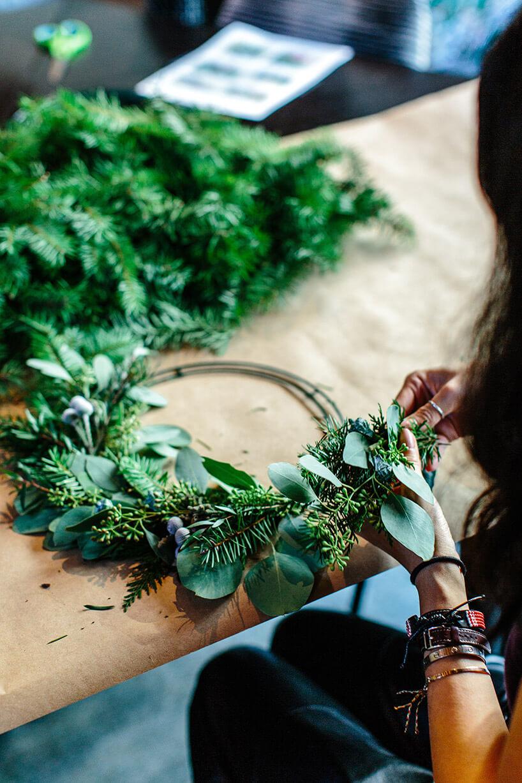 kobieta siedząca przy stole irobiąca wianek zzielonych liści