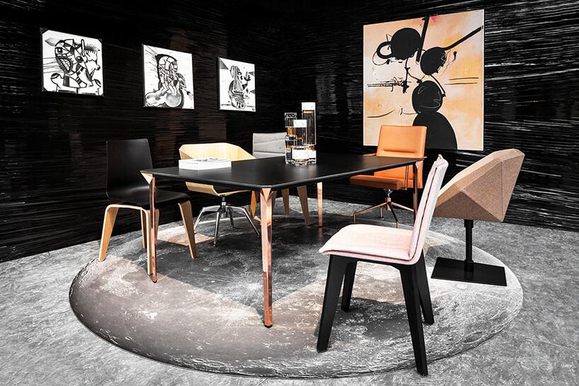 ciekawie zaprojektowane różne krzesła na tle czarnych ścian