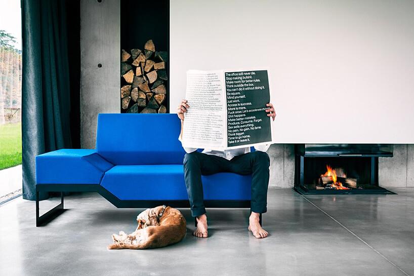 mężczyzna czyta gazetę na niebieskiej sofie