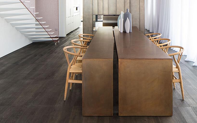 długi drewniany stół podzielony wzdłuż zdrewnianymi krzesłami