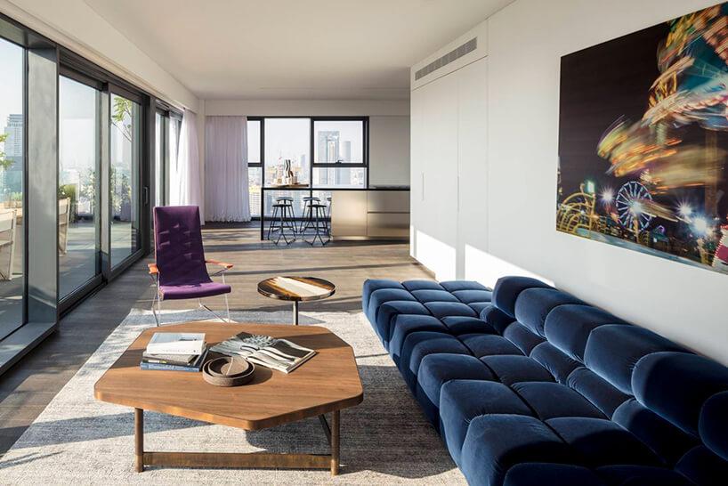 elegancki apartament od Anderman Architects wyjątkowy salon zdużą niebieską sofą ifioletowy fotelem przy niskim drewnianym stoliku