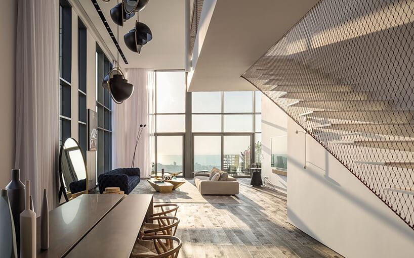 oświetlony elegancki apartament od Anderman Architects wyjątkowy salon zwysoką przeszkloną ścianą