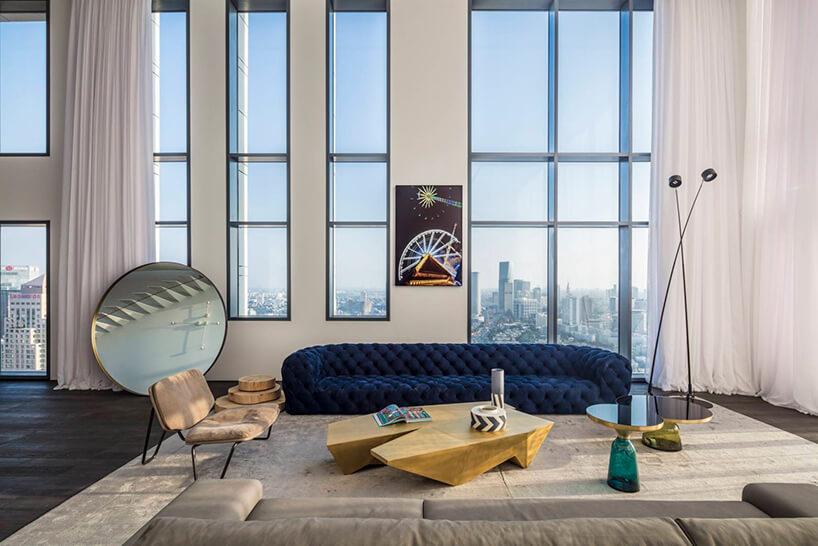 elegancki apartament od Anderman Architects długa niebieska sofa przy drewnianym stoliku obok dużego okrągłego lustra na tle widoku na Tel Awiw