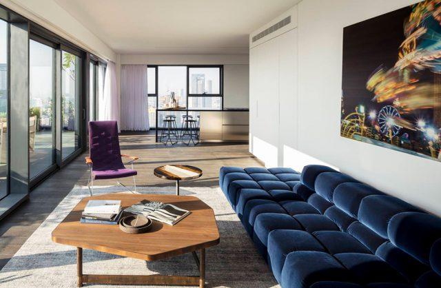 elegancki apartament od Anderman Architects wyjątkowy salon z dużą niebieską sofą i fioletowy fotelem przy niskim drewnianym stoliku