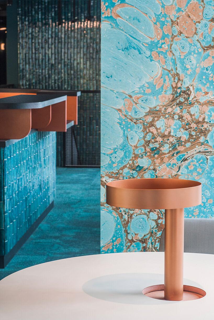 turkusowo-brązowa ściana jako tło dla stolika