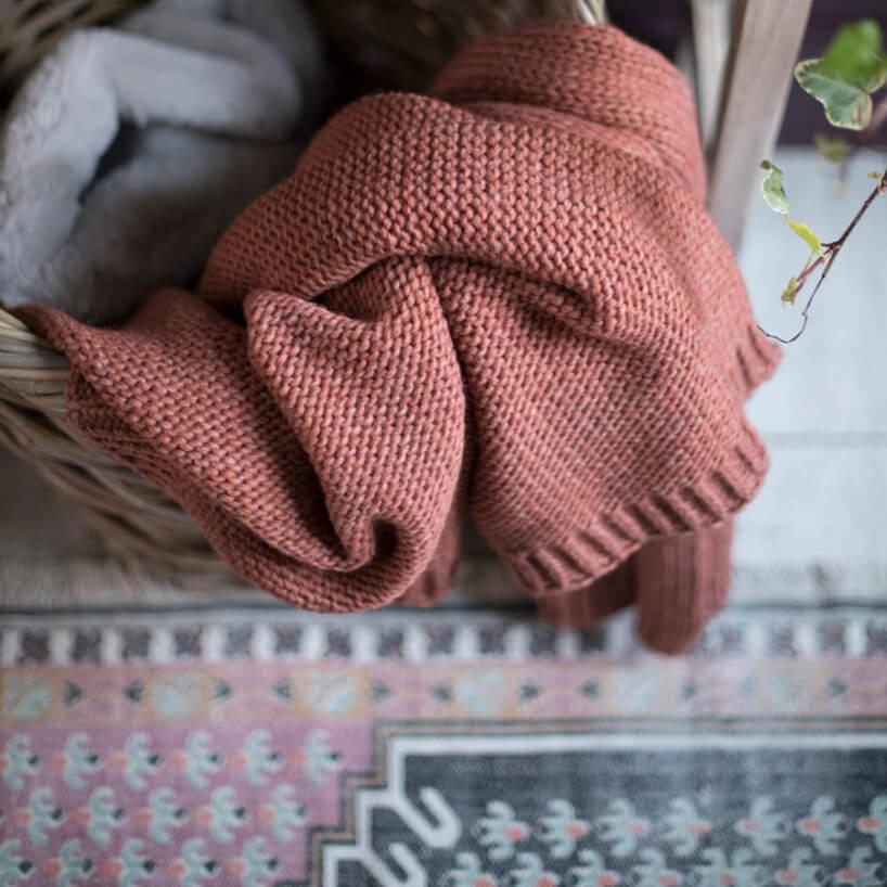 bordowy dziergany koc przewieszony przez wiklinowy wysoki kosz