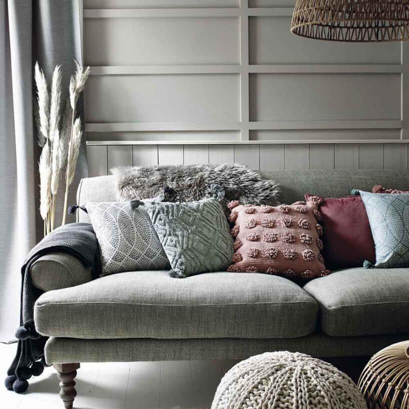szara sofa na drewnianych krótkich nogach zpięcioma poduszkami oróżnym kolorze ifakturze materiału