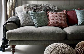 szara sofa na drewnianych krótkich nogach z pięcioma poduszkami o różnym kolorze i fakturze materiału