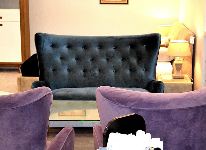 czarna sofa zwysokim oparciem jak tło dla fioletowych krzeseł materiał obiciowy Italsenso