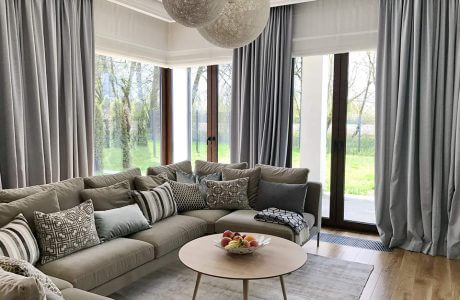 duży salon z panoramicznymi oknami i dużym szarym narożnikiem z wieloma poduszkami